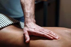 Main praticien - Patiente allongé avec un tissus à rayures bleu et blanc - Reboutement - Guérisseur - Magnétiseur